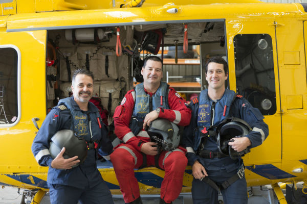 Group photo of the pilot, air crew and paramedic standing in front of the RAC Rescue helicopter