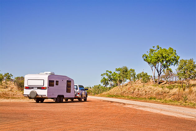 A caravan and vehicle pulling out of a rest area