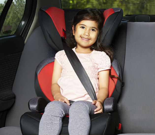 A  four year old girl in a booster seat