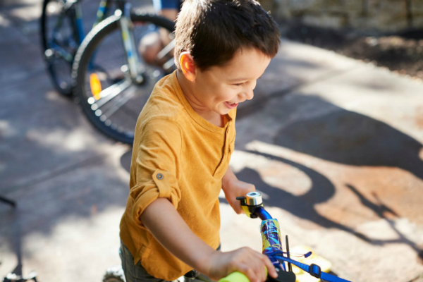 Child in driveway with bicycle